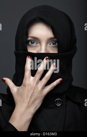Woman in black ninja dress with manicure - Stock Photo