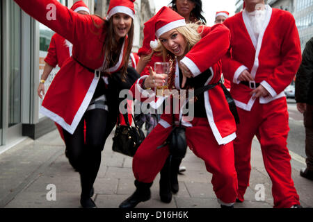 London, UK. Sunday 9th December 2012. A flash mob of Santas descends play to camera. Christmas celebrated here with - Stock Photo