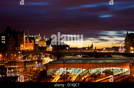 Sunset over Edinburgh's Waverley station and the festive city centre showing the christmas tree on the Mound and - Stock Photo