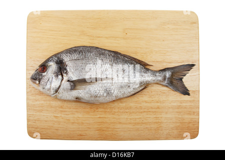 Whole sea bream fish on a wooden food preparation board isolated against white - Stock Photo