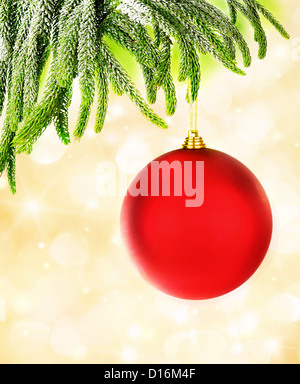 Picture of red Christmastime bubble hanging on fresh green fir branch, holiday decorations isolated on yellow blur - Stock Photo