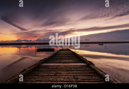 The sun sets over an old wooden jetty on the Fleet lagoon in Dorset with clouds reflected in the still water.