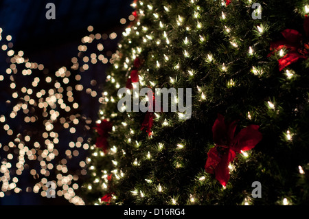 close up of a christmas tree decorated with lights and red ribbon stock photo