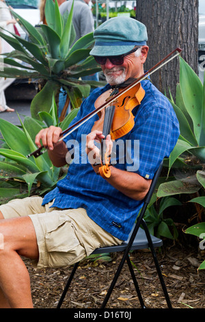 An elderly man with a hat plays the violin while seated at the Farmers' Market in 'Santa Barbara', California - Stock Photo