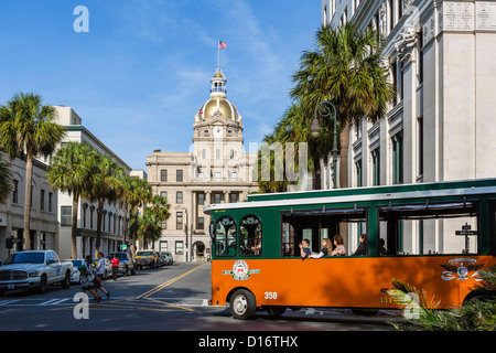 Old Town Trolley Tours trolley on Bull Street with City Hall behind, Savannah, Georgia, USA - Stock Photo