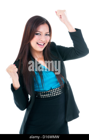 Happy young businesswoman cheering with clenched fists - Stock Photo