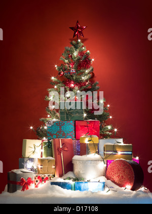 beautifully decorated christmas tree surrounded by a pile of colorful presents covered with snow on red background - Stock Photo