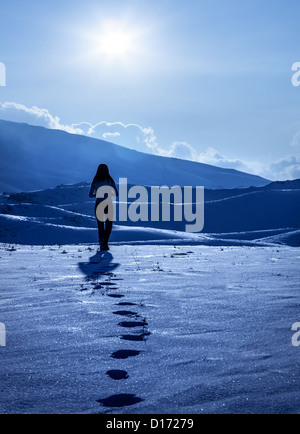 Image of lonely woman silhouette at winter mountains, footprints on the snow, enjoying wintertime nature view,one - Stock Photo