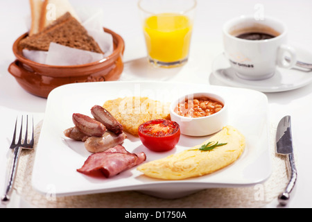A traditional breakfast consists of bacon, sausage, tomato, hash browns, egg & baked beans, with orange juice, coffee - Stock Photo