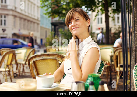Woman enjoying the pleasant morning with a cup of coffee outdoors in a street cafe - Stock Photo