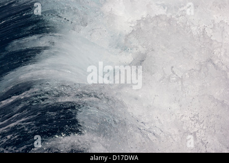 Waves breaking, wake off the side of a cargo ship in deep ocean - Stock Photo