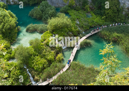Tourists walking along wooden walkways in Plitvice Lakes National Park in Croatia. - Stock Photo