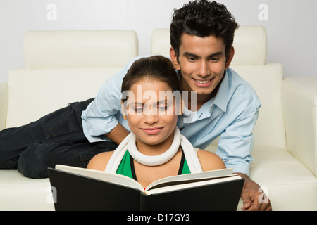 Couple looking at a photo album and smiling - Stock Photo