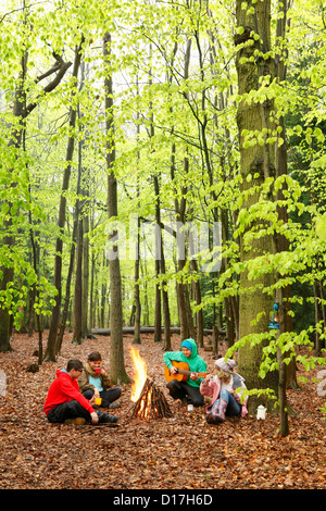 Friends sitting around campfire together - Stock Photo
