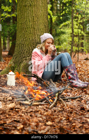 Woman drinking coffee by campfire - Stock Photo