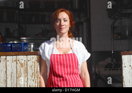 Woman in apron working outdoors - Stock Photo