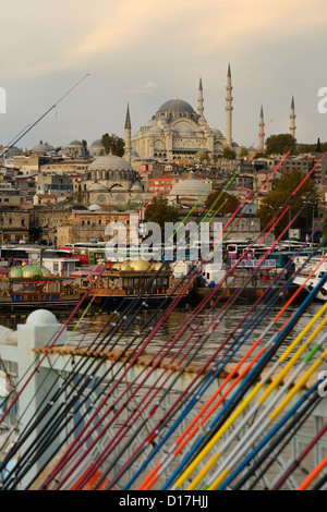 Fishing rods for sale on Galata Bridge over Golden Horn with Suleymaniye Mosque Istanbul Turkey - Stock Photo