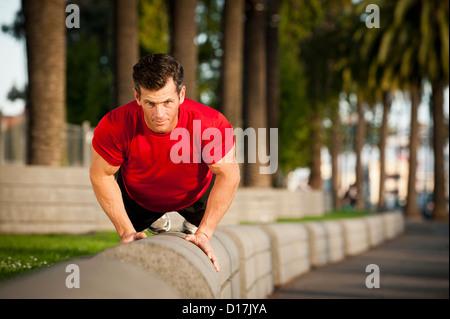 Man exercising on city street - Stock Photo