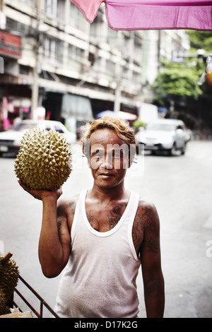 Man selling durian fruit on street - Stock Photo