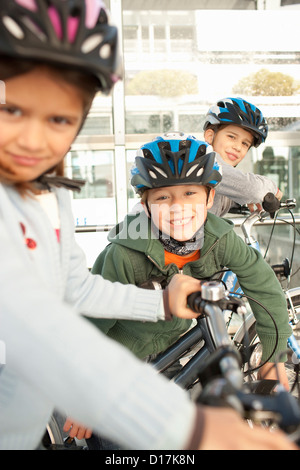 Children riding bicycles in city tunnel - Stock Photo