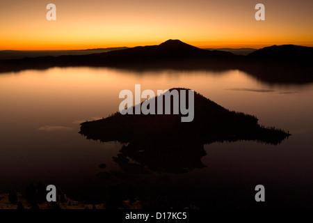 View across Crater Lake from Watchman Overlook at sunrise with Wizard Island in the foreground in Crater Lake National - Stock Photo