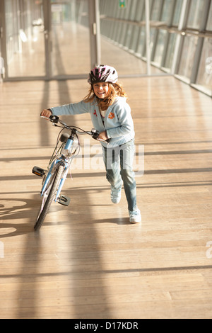 Girl walking bicycle in city tunnel - Stock Photo