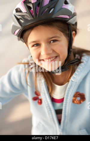 Girl wearing bike helmet outdoors - Stock Photo