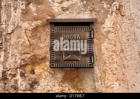 Old mailbox on ancient stone wall - Stock Photo