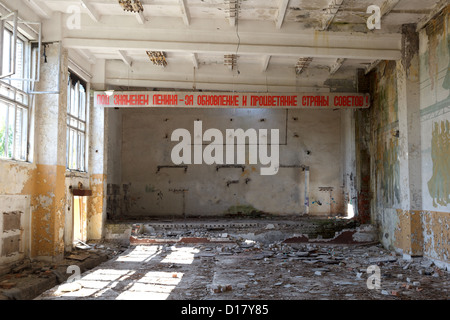 abandoned building, a former Soviet military base. Lenin slogan, still on the ceiling - Stock Photo