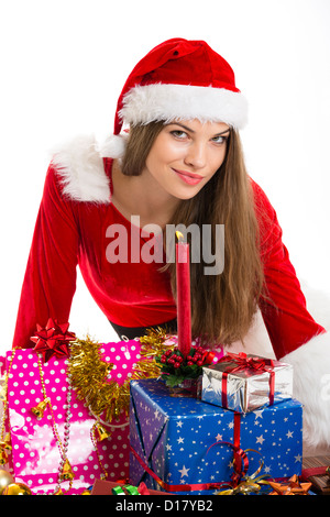 Beautiful Christmas girl wearing Santa Claus clothes with many gift boxes and burning candle over white background. - Stock Photo