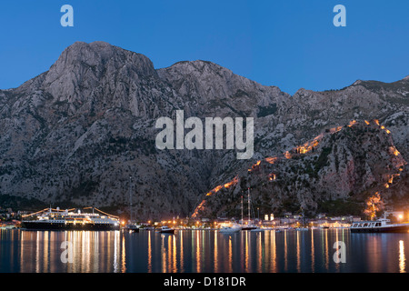 Dusk view of Kotor Bay, Kotor town and the fortifications overlooking the town in Montenegro. - Stock Photo
