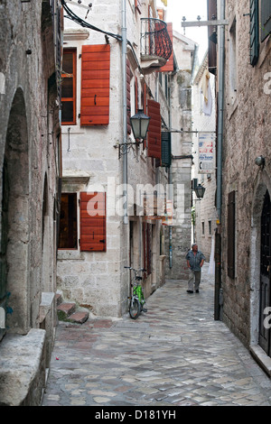 Man walking through the narrow cobbled streets of the old town of Kotor in Montenegro. - Stock Photo