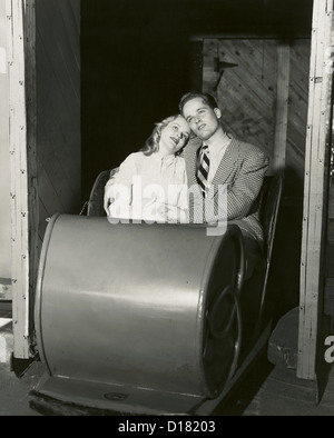 Lovesick teenage couple sitting in carnival ride, 1950's-1960's - Stock Photo