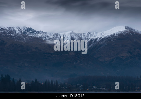 Clouds gathering over snowy mountains - Stock Photo
