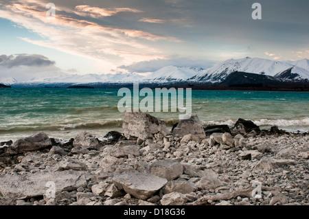 Waves washing up on rocky beach - Stock Photo