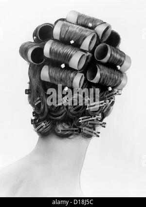 1960s bouffant hair styles were created with big rollers on top of the head and pin curls to create a soft flip - Stock Photo