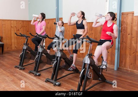 Women on exercise bikes, drinking from bottles - Stock Photo