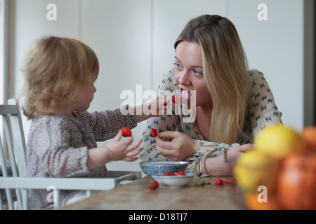 Daughter feeding mother strawberries - Stock Photo