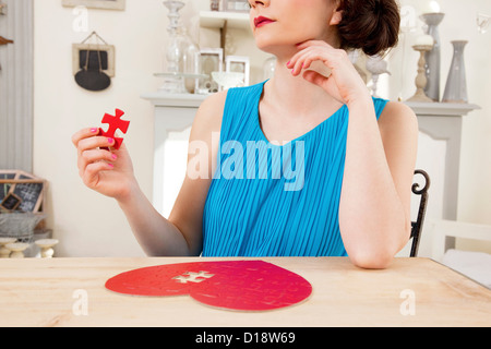 Woman doing heart shaped jigsaw puzzle holding piece - Stock Photo