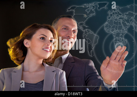 Businesspeople touching world map - Stock Photo