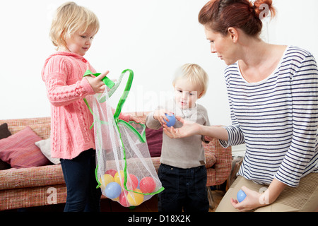 Mother and children playing with plastic balls - Stock Photo
