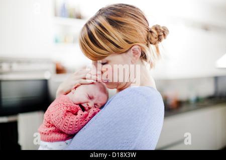 Mother holding newborn daughter - Stock Photo