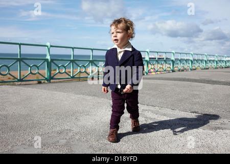 Little boy walking promenade in mod clothing - Stock Photo