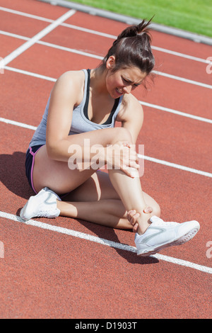 Female runner with ankle injury - Stock Photo