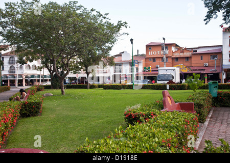 view across green lawn & paths of zocalo to modest buildings lining south side of square in small town of La Crucecita - Stock Photo