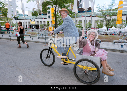 Comedian dressed and made up as an elderly man carrying his wife in a three wheeler. - Stock Photo