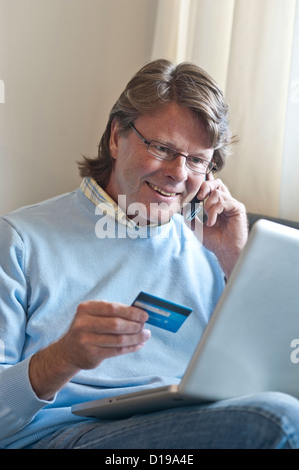 Mature man at home making a card financial transaction on line using his laptop computer and an iPhone smartphone - Stock Photo