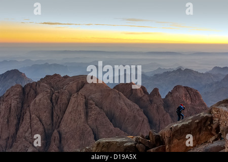 An individual watches sunrise from the edge of a cliff on top of Mount Sinai in the Sinai desert - Stock Photo