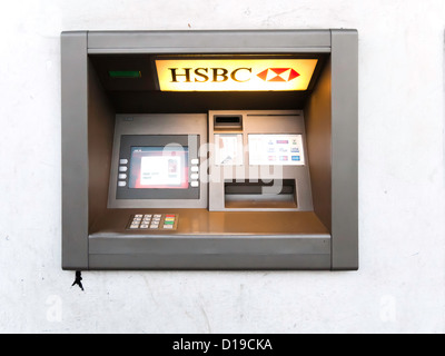 Cash Machine ATM Hole in the Wall Automatic Teller HSBC Bank lit in evening light - Stock Photo