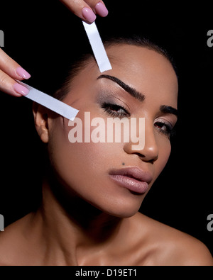 Woman having face lifted with tape - Stock Photo